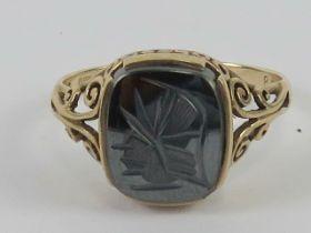 A 9ct gold hematite signet ring having carved centurion design upon, hallmarked 375, size T, 3.4g.