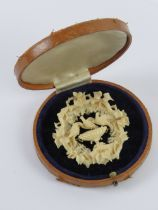 A superbly detailed 19th century carved ivory brooch having central Pliny doves stood upon a