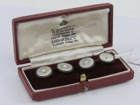 A pair of 9ct gold mother of pearl and seed pearl cuff links presented within Garrard & Co Ltd box,