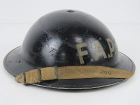 A WWII Brodie helmet FAP (First Aid Post) with liner and chinstrap.
