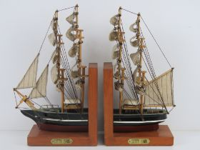 A pair of contemporary bookends in the form of the Cutty Sark complete with fabric sails,