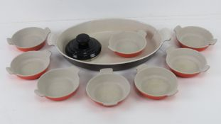 Le Cruset; a large oval oven dish together with a set of eight individual dishes and a teapot lid.