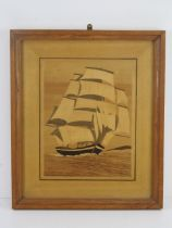 A large marquetry picture of a masted ship with sails on the sea, framed and glazed,