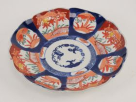 An Oriental dish decorated in blues and reds having fluted border, 21cm dia,