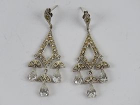 A pair of silver cocktail earrings havin