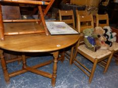 AN OAK GATE LEG DINING TABLE AND FOUR RUSH SEAT DINING CHAIRS.