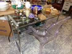 A CHROME AND GLASS DESK AND A PERSPEX ARM CHAIR.