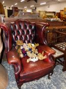 A LEATHER UPHOLSTERED WING ARM CHAIR.