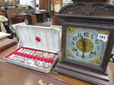 AN ANTIQUE STRIKING MANTLE CLOCK, AND BOXED DESSERT CUTLERY.