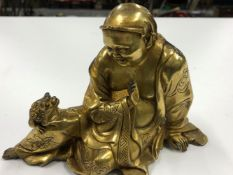 A EASTERN GILT BRONZE FIGURE OF A DEITY SEATED CONVERSING WITH A TOAD TOGETHER WITH A GILT BRASS