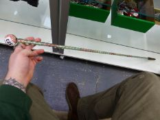 A SPIRAL TWIST GLASS WALKING CANE FILLED WITH COLOURED HUNDREDS AND THOUSANDS. H 116cms.