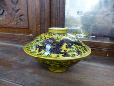 AN ORIENTAL PORCELAIN SMALL DISH AND COVER WITH DRAGON DECORATION ON A YELLOW GROUND.