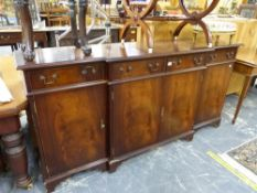 A REPRODUCTION MAHOGANY BREAK FRONT SIDE BOARD.