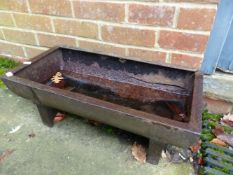 A SMALL CAST IRON FEED TROUGH
