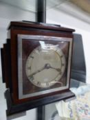 AN ART DECO MAHOGANY AND EBONY CASED MANTEL CLOCK RETAILED BY J HALL & Co. MANCHESTER, THE TIMEPIECE