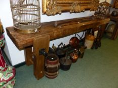 AN ANTIQUE RUSTIC LONG WORKBENCH WITH FITTED VICE 234 CM WIDE X 75 CM HIGH