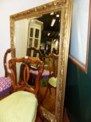 A LARGE BEVELLED MIRROR WITH FLORAL GILT FRAME 136 X 107 CM