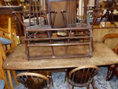 AN ERCOL ELM DINING TABLE, FOUR CHAIRS, AND A PLATE RACK.
