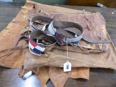 A GROUP OF AFRICAN LEATHER BEADED BELTS AND HANGINGS.