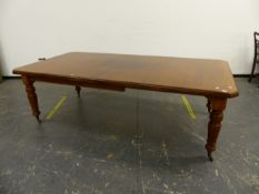 A VICTORIAN MAHOGANY WIND OUT EXTENDING DINING TABLE ON TURNED LEGS COMPLETE WITH TWO LEAVES AND