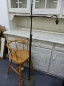A CHILDS HIGH CHAIR AND A STANDARD LAMP.