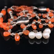 A SILVER AND ORANGE HARDSTONE GRADUATED AND WOVEN REVIVALIST STYLE NECKLACE APPROX LENGTH 41cms,