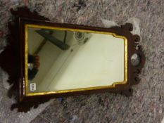 AN ANTIQUE FRET FRAMED WALL MIRROR WITH BEVELLED GLASS PLATE. H 82 X W 46cms.