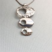 A SILVER HAMMERED AND POLISH FINISHED GRADUATING PENDANT SUSPENDED ON A SILVER SNAKE CHAIN.