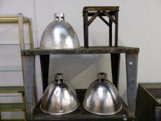 THREE ALUMINIUM INDUSTRIAL LIGHT SHADES, AND AN ALUMINIUM STAND. SHADES APPROX DIAMETER 54cms DROP