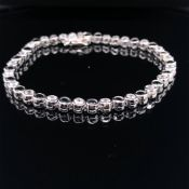 A SILVER RUBOVER SET LINE BRACELET WITH BLUE AND WHITE CUBIC ZIRCONIAS, COMPLETE WITH TWO FIGURE