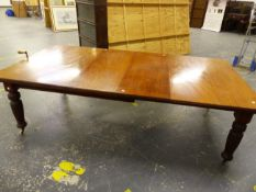 A LATE VICTORIAN MAHOGANY WIND OUT EXTENDING DINING TABLE ON TURNED REEDED LEGS, COMPLETE WITH TWO