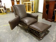 A LATE VICTORIAN DARK LEATHER ADJUSTABLE ARM CHAIR WITH SLIDE UNDER FOOT REST, THE ARMS HINGED AT