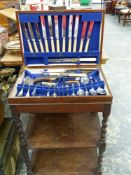 A PART SET PLATED CANTEEN OF CUTLERY ON A FITTED OAK TWO TIER STAND.