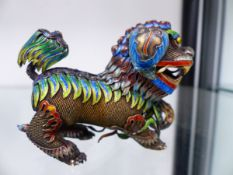 AN EASTERN SILVER AND ENAMELLED FOO DOG.