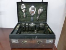 A VINTAGE LEATHER TRAVELLING DRESSING CASE WITH SILVER PLATED FITTINGS.