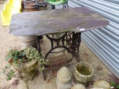 A SLATE TOP IRON BASE GARDEN TABLE.