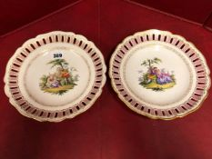 A PAIR OF MEISSEN PLATES, THE ARCADE PIERCED PINK RIMS ENCLOSING COUPLES IN LANDSCAPES, CROSSED