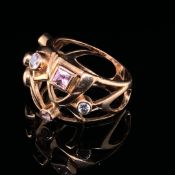A RUSSIAN HALLMARKED ROSE GOLD GEM SET RING TESTED AS 14ct GOLD. SET WITH EIGHT RUB OVER SET PINK,