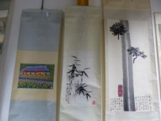 THREE CHINESE SCROLLS PRINTED WITH BAMBOO. 65.5 x 35cms. WITH AN AERIAL VIEW OF A PINK TAXI PARKED
