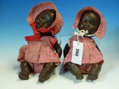 TWO SIMILAR ARMAND MARSEILLE BLACK DOLLS IN RED GINGHAM DRESSES AND BONNETS. H 27cms.