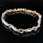 A 9ct GOLD, BLUE TOPAZ AND DIAMOND BRACELET, COMPLETE WITH A FIGURE OF EIGHT SAFETY CLASP. LENGTH