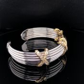 AN 18ct WHITE GOLD AND DIAMOND TORQUE STYLE BANGLE. THE THREE YELLOW GOLD KISSES EACH DIAMOND SET