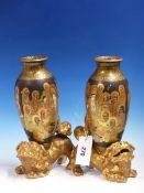 A PAIR OF SATSUMA VASES PAINTED WITH KWANNON AMONGST LOHANS ON A BLACK GROUND AND SUPPORTED ON THE