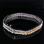 AN 18ct WHITE GOLD DIAMOND AND MULTICOLOURED RAINBOW SAPPHIRE LINE BRACELET. THE ARRAY OF
