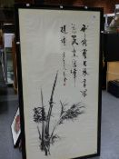 AN ORIENTAL INK SCROLL PAINTING OF BAMBOO WITH AN INSCRIPTION AND RED SEAL ABOVE, NOW IN A BLACK