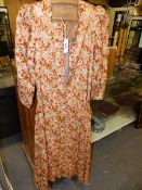 AN OTTOMAN BEIGE COTTON KAFTAN SEWN IN OCHRES AND PINKS WITH GREEN LEAVED FLOWERS, BUTTONS DOWN