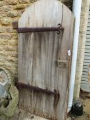 AN ARTS AND CRAFTS TEAK THREE PLANK ROUND ARCHED DOOR WITH MASSIVE IRON HINGES AND STRING PULL LATCH