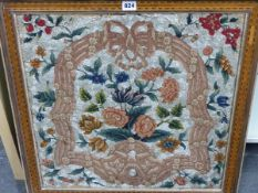A MID19th C. WOOL AND BEADWORK PICTURE OF FLOWERS WITHIN A PINK AND BROWN RIBBON FRAME, THE GREY AND