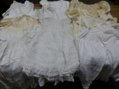 A COLLECTION OF CHRISTENING GOWNS, TODDLER CLOTHES, LACE TRIMMED BIBS, A SHAWL AND TWO SILK JACKETS