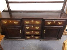 AN 18TH CENTURY COUNTRY OAK DRESSER BASE WITH CENTRAL DRAWERS AND PANEL SIDES.